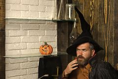 Halloween man wizard sitting in black witch hat with pumkin. On shelf. Magic, evil spell, wizardry and witchcraft. Holiday celebration concept royalty free stock photos