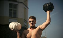 Halloween man with zombie face sunny outdoor. Halloween guy with white and black traditional pumpkin. demon with muscular body and makeup. Holiday and stock photos