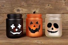 Halloween mason jar candle holders. Mason jar Halloween candle holders against an old wood background Stock Image