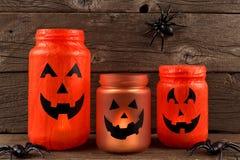 Halloween mason jar Jack o Lanterns. Mason jar Halloween Jack o Lanterns against an old wood background Stock Photo