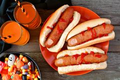 Halloween meal scene with hot dog fingers, drinks and candy Royalty Free Stock Photo