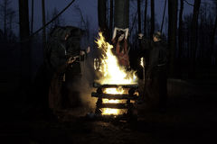 Halloween. Men in black clothes, burn the witch at the stake at Stock Images