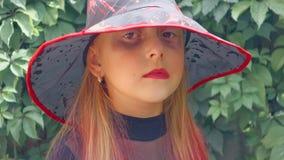 Halloween Menina adolescente vestida como uma bruxa má, com bordos e as equimoses vermelhos sob seus olhos vídeos de arquivo