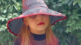 Halloween Menina adolescente vestida como uma bruxa má, com bordos e as equimoses vermelhos sob seus olhos video estoque