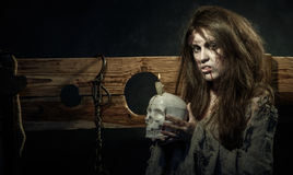 Halloween. The Middle Ages. Portrait of a terrible evil witch wi. Th a skull in his hands Royalty Free Stock Photos