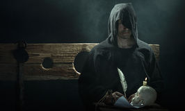 Halloween. The Middle Ages. Warlock with a skull and a candle. On a table stock photography