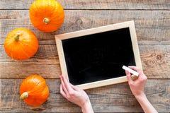 Halloween-Modell Tafel nahe Kürbisen auf Draufsicht des hölzernen Hintergrundes Lizenzfreie Stockbilder