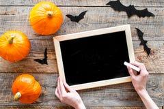 Halloween-Modell Tafel nahe Papierschlägern und Kürbisen auf Draufsicht des hölzernen Hintergrundes Stockfoto