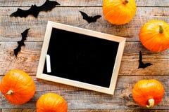 Halloween-Modell Tafel nahe Papierschlägern und Kürbisen auf Draufsicht des hölzernen Hintergrundes Lizenzfreie Stockbilder