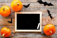 Halloween-Modell Tafel nahe Papierschlägern und Kürbisen auf Draufsicht des hölzernen Hintergrundes Stockbilder