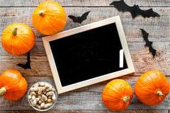 Halloween-Modell Tafel nahe Papierschlägern und Kürbisen auf Draufsicht des hölzernen Hintergrundes Lizenzfreies Stockfoto