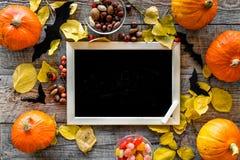 Halloween-Modell Tafel nahe Papierschlägern und Kürbisen auf Draufsicht des hölzernen Hintergrundes Lizenzfreie Stockfotografie