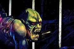 Halloween Monster. Creepy Halloween monster behind grid Stock Photo