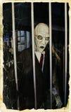 Halloween Monster. Creepy Halloween monster behind grid Stock Image