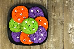 Halloween monster eyeball cookies against rustic wooden background Stock Image