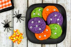 Halloween monster eyeball cookies against rustic wooden background Stock Images