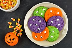 Halloween monster eyeball cookies on plate against black background Stock Photo