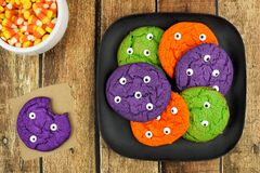 Halloween monster eyeball cookies on plate against rustic wood. Spooky Halloween monster eyeball cookies on a plate against rustic wood background with candy Stock Photo
