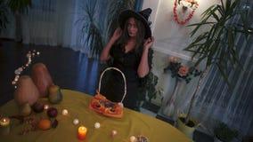 Halloween Mooi meisje die op heksen` s hoed proberen stock footage