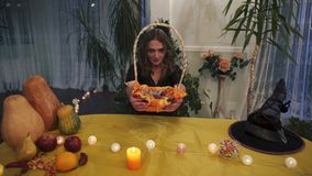 Halloween Mooie heks die een mand van snoepjes houden stock videobeelden