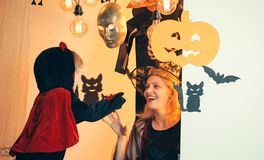 Halloween mother with a carved Pumpkin and magic light. Witch hat for mother and son. Children play with mother pumpkins. And treat. Halloween decoration and royalty free stock photos