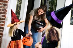 Halloween: Mother Hands Out Candy to Little Girl Witch royalty free stock images