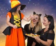 Halloween A mulher dois em gatos pretos dos trajes é tratada à bruxa pequena com os doces Menina bonita no traje de Dia das Bruxa Foto de Stock Royalty Free