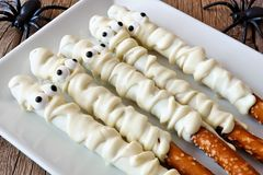 Halloween mummy candy dipped pretzel rods, on plate Stock Images