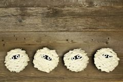 Halloween mummy cupcakes on rustic wood Stock Photo