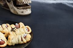 Halloween Mummy Hot Dogs Wrapped in Croissant Rolls. Fun food for kids. Halloween mummy hot dogs. Wieners wrapped in croissant rolls to look like mummies on a royalty free stock photo