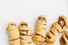 Halloween Mummy Hot Dogs Wrapped in Croissant Rolls. Fun food for kids. Halloween mummy hot dogs. Wieners wrapped in croissant rolls to look like mummies on a stock photos