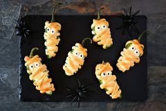 Halloween mummy jalapeno poppers on a slate server. Halloween mummy jalapeno poppers, top view on slate server with spiders stock images