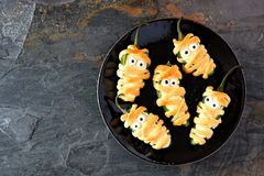Halloween mummy jalapeno poppers, top view on dark stone. Plate of Halloween mummy jalapeno poppers, top view on with a dark stone background royalty free stock photos