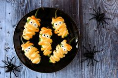 Halloween mummy jalapeno poppers, top view on dark wood. Plate of Halloween mummy jalapeno poppers, top view on with a dark wood background with spiders stock images