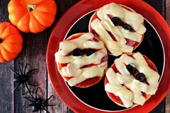 Halloween mummy mini pizzas on black and orange plate Stock Photos