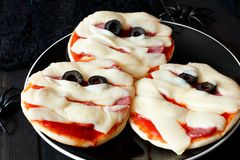 Halloween mummy mini pizzas on black plate against dark wood Royalty Free Stock Photos