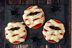 Halloween mummy mini pizzas on slate server with spiders Stock Photo
