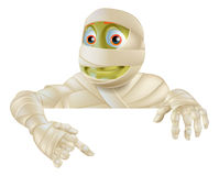 Halloween Mummy Pointing Down. An illustration of a cartoon Halloween Mummy pointing down at a sign or scroll Stock Image
