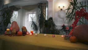 Halloween. Mystical table for Halloween. Halloween. Magic table for Halloween. Burning candles, pumpkins, knives and fruits on the magic table. The camera moves stock video