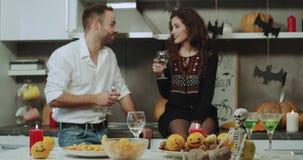 Halloween-nacht thuis rond heeft een paar een romantische tijd het drinken wijn, kaarsen en pompoenen Geschoten op Rood Heldendic stock video