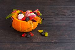 Halloween natural pumpkin with various candies over wooden background. With copy space royalty free stock photos