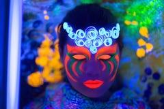 Halloween neon art. Creative woman model shine blue green orange colors. Bright conceptual art make-up glows under ultraviolet light. Club disco neon party time Stock Photos