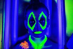 Halloween neon art. Creative woman model shine blue green orange colors. Bright conceptual art make-up glows under ultraviolet light. Club disco neon party time Royalty Free Stock Photography