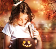 Halloween-nette kleine Hexe mit Kasten Stockfoto