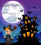 Halloween night background with little boy witch holding broomstick and scary castle in graveyard Stock Image