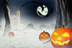 Halloween. The night of Halloween. Bats and Halloween pumpkins on the background of the gloomy house and the forest in the fog Royalty Free Stock Images
