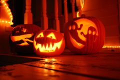 Halloween night pumpkins jack o lantern carved with candle light orange. Here is a photo of three carved jack o lanterns on the front porch. Wood. Chipped paint Stock Photos
