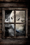 Halloween night ravens. Flying in front the moon and clouds, view through an old wooden cabin window Royalty Free Stock Image