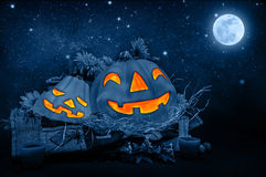 Halloween night. Scary carved pumpkin head glowing in dark starry night, full moon, traditional october holiday, horror concept stock illustration