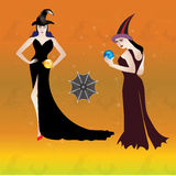 Halloween night with two sexy witch holding magic glass in their Stock Photo